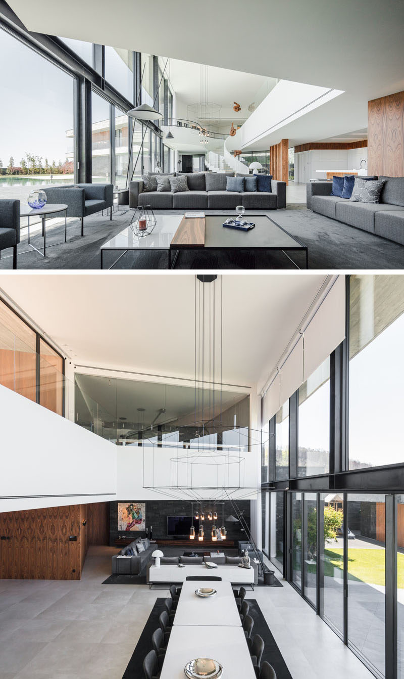 Inside this modern house, the living room, with a grey accent wall and dark grey furniture, is located at one end of the home. Large sliding glass doors open the interior to the outdoor patio and swimming pool. #LivingRoom #OpenPlanInterior #ModernInterior
