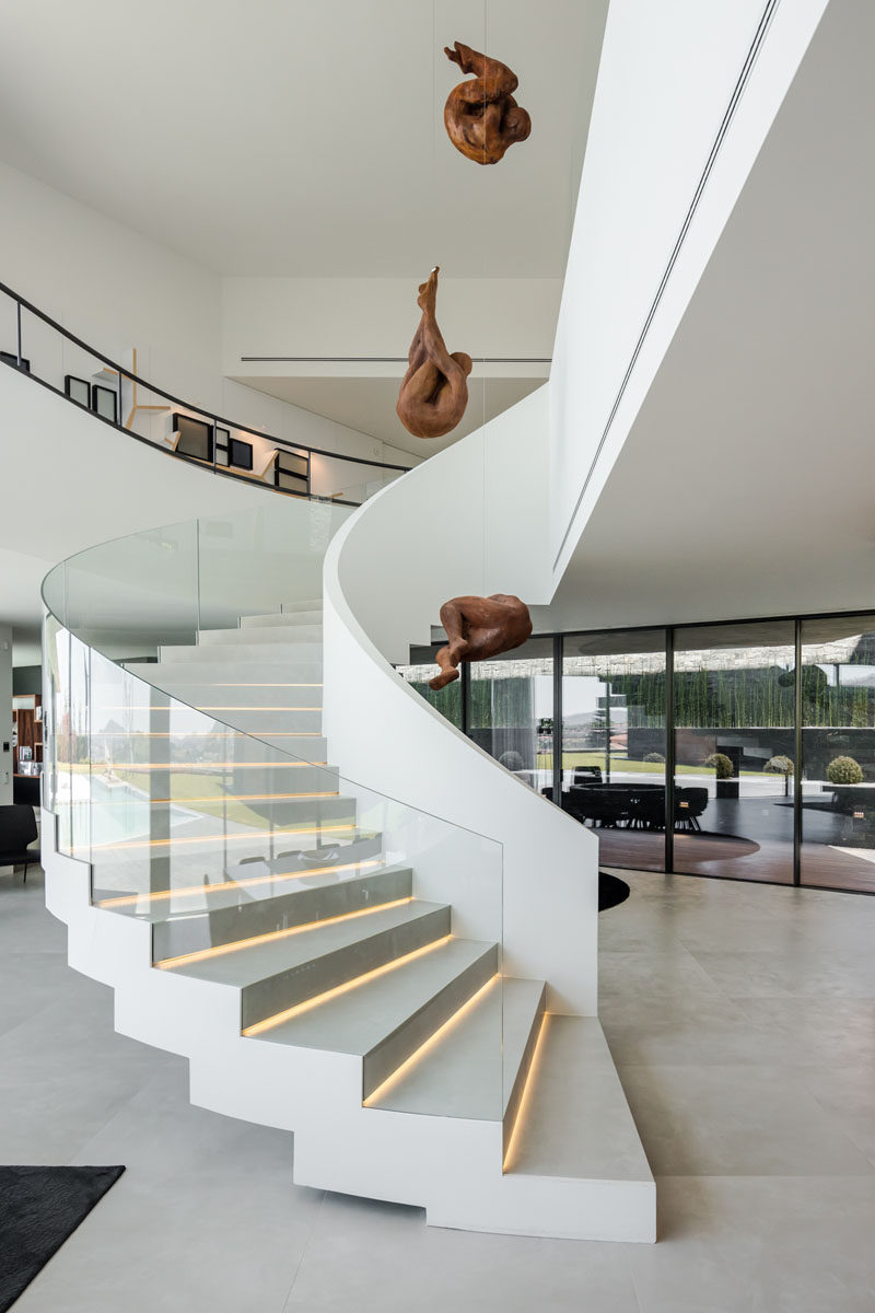 A curved white staircase with glass handrails and hidden lighting connects the various levels of this modern house. #Staircase #Stairs #CurvedStairs #ModernStairs