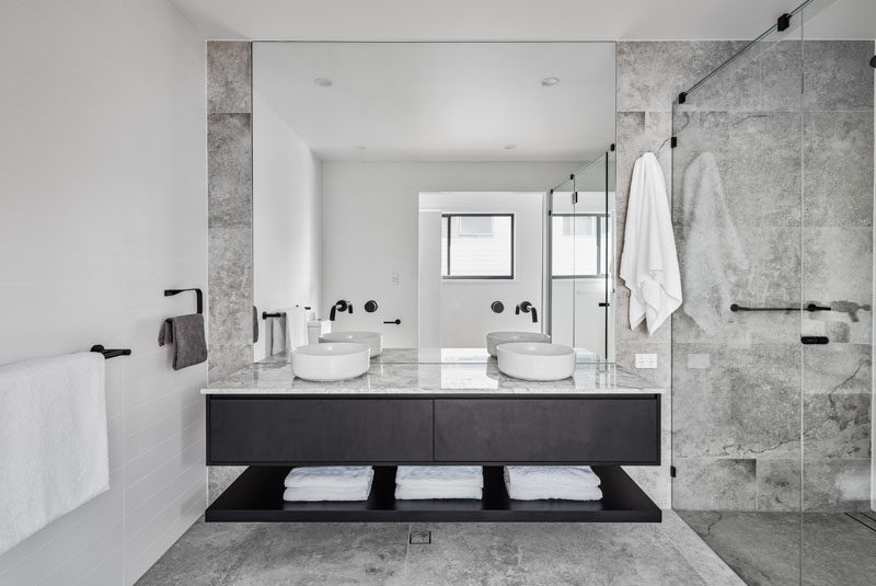A simple color palette of grey, white, and black has been used in this modern bathroom, while a large mirror reflects the light from the window. #ModernBathroom #BathroomDesign