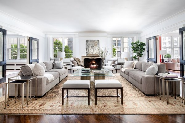 Just off the foyer is a spacious living room, which is anchored by expansive windows and a wood-burning fireplace. The light-filled area is flanked by a corner library and dining room, creating a seamless flow of open space.