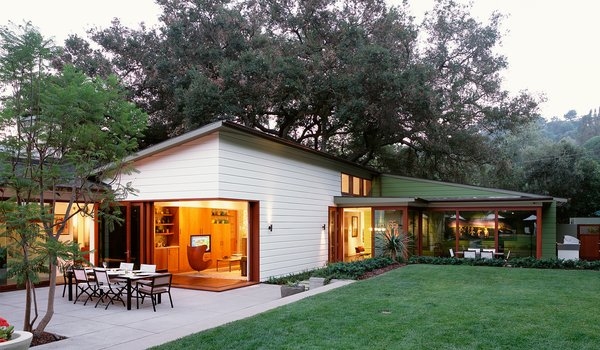 The large pocket doors of Mandeville Canyon House open up the corner of the living room to the concrete terrace and lawn beyond. This house, designed by Dutton Architects, is perfect for informal living and taking advantage of the southern California climate.