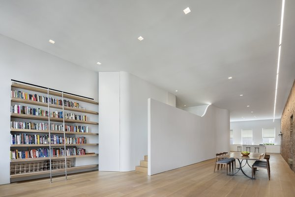 Architect Julian King's creative approach to incorporating a bedroom without sacrificing natural light: creating a narrow mezzanine with undulating walls that act as both art and a link to the building's past as a silk warehouse.