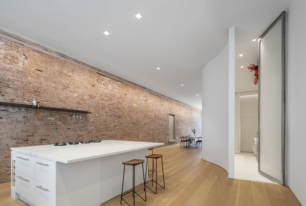 The new layout of the apartment allows for light to stream in from the north and the south. The original brick wall is washed with a continuous, slim LED light. The door to the bathroom is a custom 13-foot-high sandblasted pivot door.