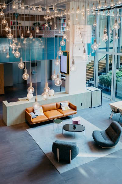 An aerial view of the lobby, awash in natural light from the floor-to-ceiling windows.