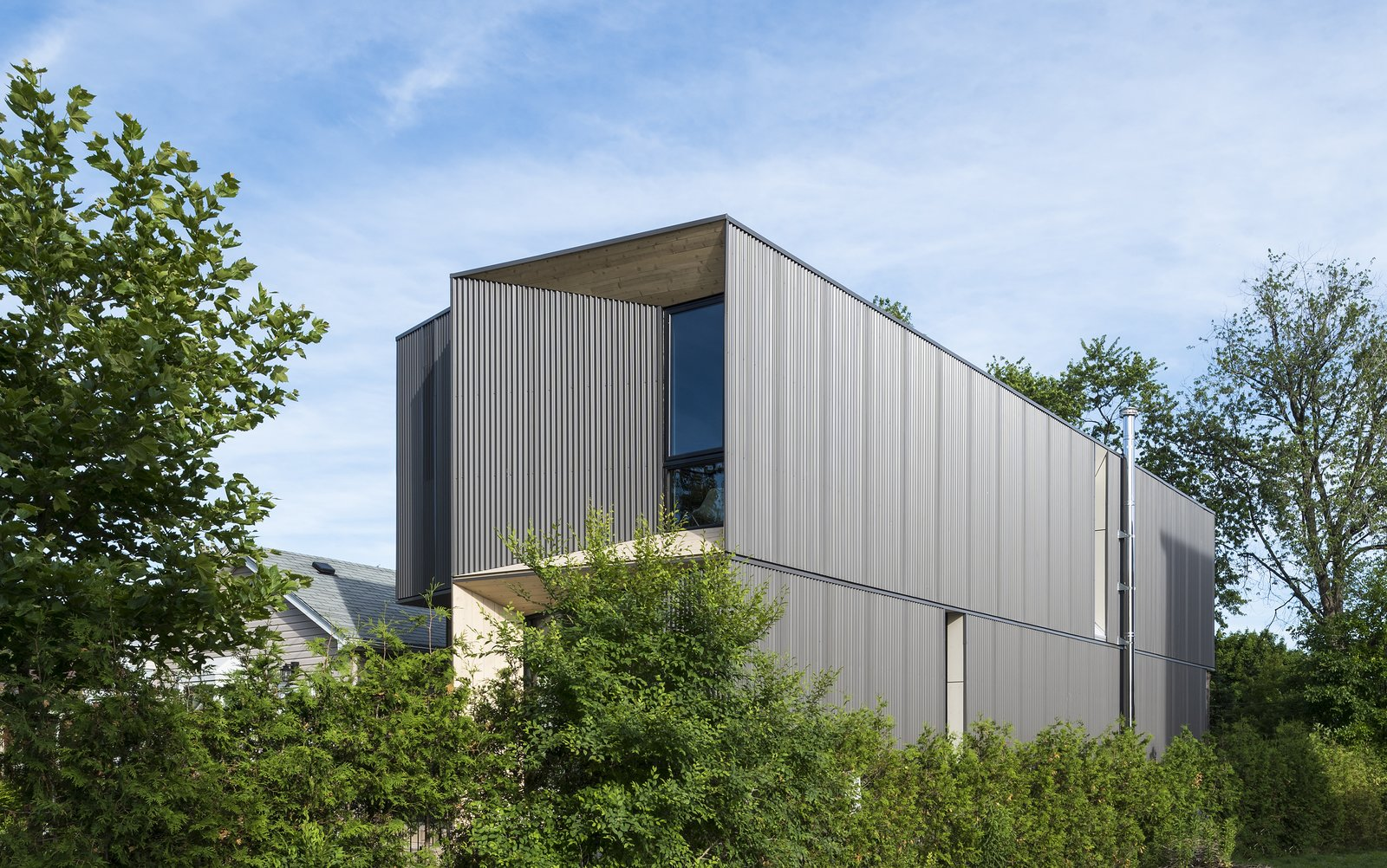 """View of the front and side of the house from the neighboring lot. The overall form of the home is broken down with light penetrating """"carves"""" into the massing."""