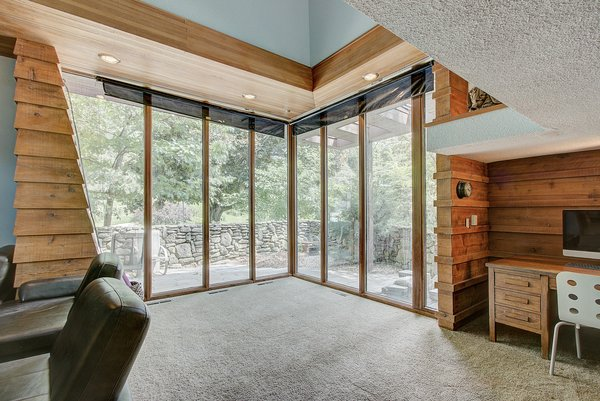 Clapboard walls in the living room meet up with a large glass wall in the corner. Overlooking a stone-walled patio, the large windows enhance the room's relationship with the outdoors.