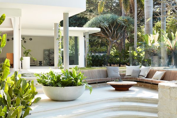 This midcentury home was originally designed by George Reeves and updated by Luigi Rosselli Architects. In the backyard, Will Dangar's landscape design places the verdant, tropical scenery at center stage.