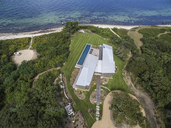An aerial view of Martha's Vineyard Retreat shows its idyllic location adjacent to the beach; the manicured lawn gives way to a forested area that leads to sandy paths down to the shoreline.