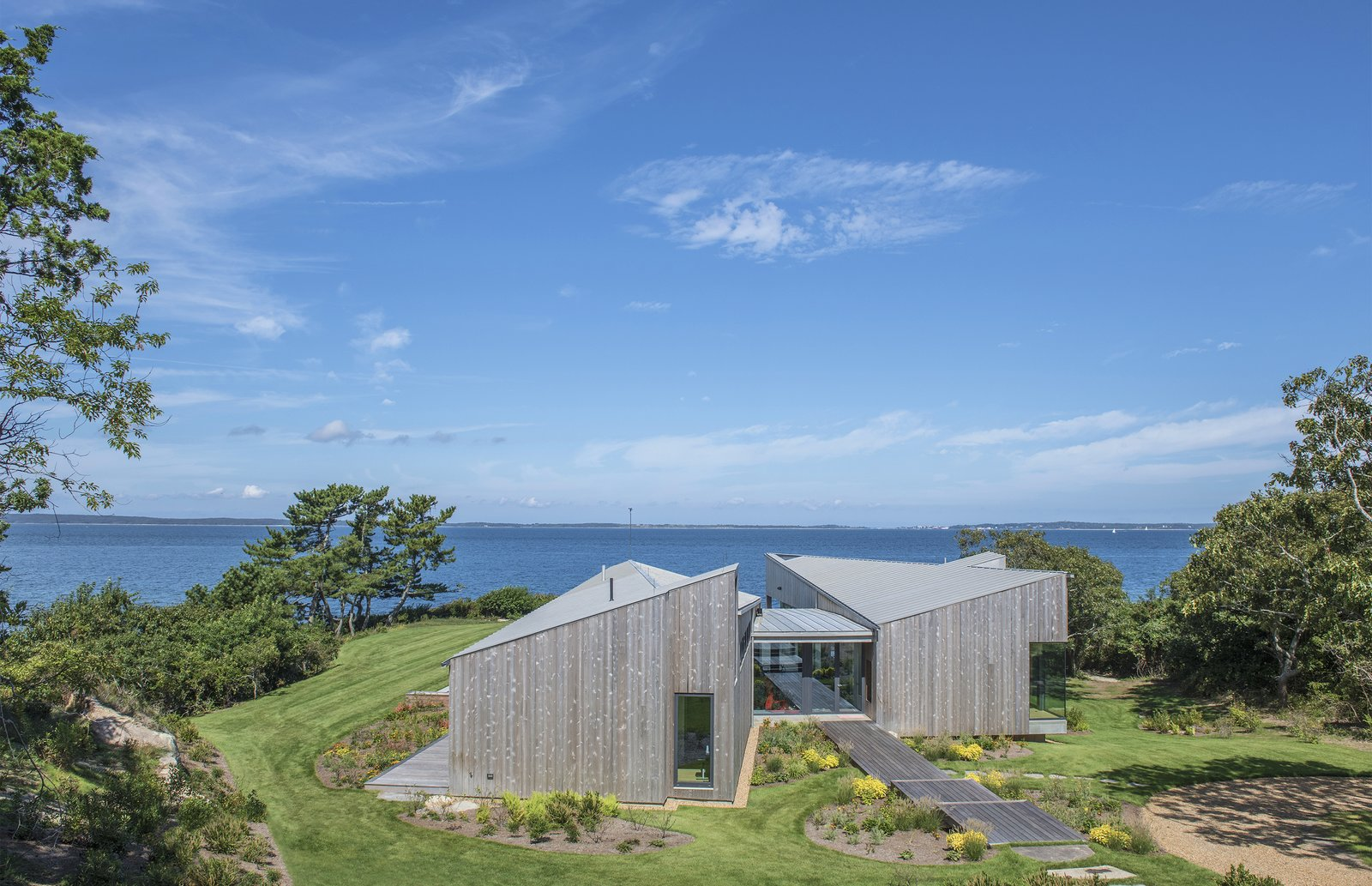 Approached from the driveway, the home is accessed along a stone path that turns into a series of wide, wooden steps. The home's angular roofline is a dramatic form against the natural backdrop, but the wood cladding connects it to the site.