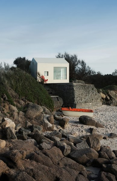 This refurbished concrete fishing shack on France's Cotentin Peninsula was originally built in the 1950s on a rock facing the sea. Its dimensions match Henry David Thoreau's log cabin in Walden—10 feet by 15 feet—and France's strict coastal regulations meant its size and shape couldn't change during restoration. So FREAKS, a Paris architecture firm, did what it could, adding champagne-colored galvanized metal cladding as insulation and two large sliding windows that open onto the horizon.