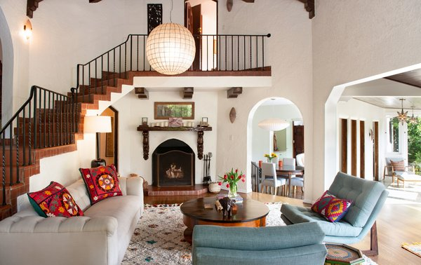 Bright, airy, and spacious, the two-story living room is steeped in historic charm, featuring the home's original wooden mantel, beamed ceilings, and open brick staircase.