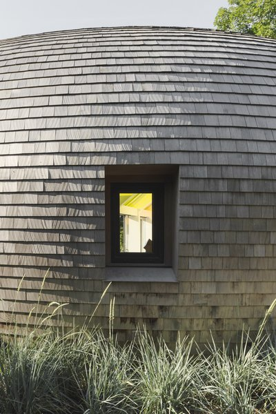 """Edwards Anker clad the home in cedar shingles in a nod to the local context, as many traditional homes on Long Island use the material. """"Because it's such an old craft, and cedar shingles have been around in Long Island for hundreds of years, they've developed technologies for double curving these shingles for a lot of curved shapes,"""" says Edwards Anker."""