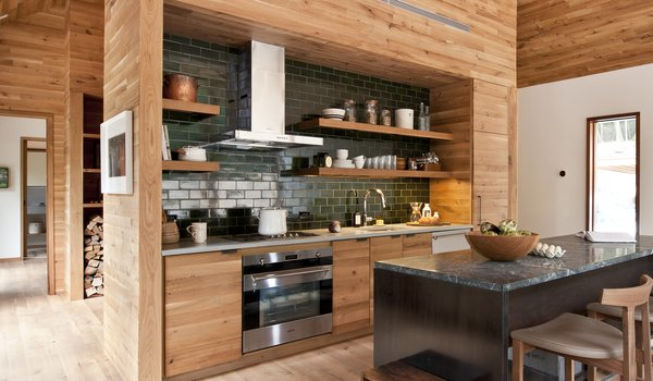 In the kitchen, dark-green subway tiles contrast with wood cabinetry and a marble-topped central island that was crafted from blackened steel and walnut.