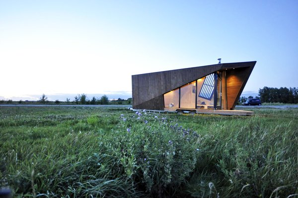 The angled tiny house is tied to the landscape through expansive windows. Its distinct shape recalls a folded leaf—a nod to the homeowner's love of nature.