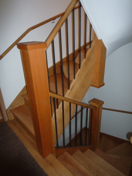 Before: The wooden staircase was cramped, lacked natural light, and created an awkward interior layout.