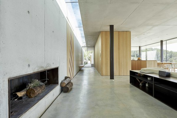 The main entry opens up to an expansive living room, while a long hallway continues behind the kitchen and leads back outside. A skylight appears to divide the home in half, creating an interplay of light, space, and form.