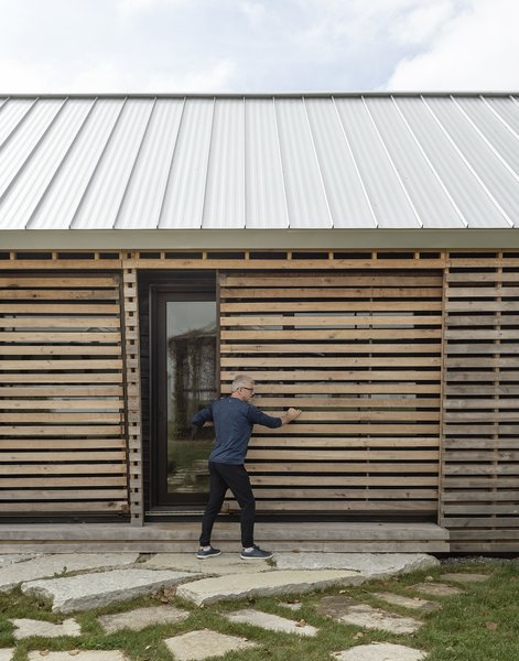 Sliding doors in the slatted shell conceal the side entry.