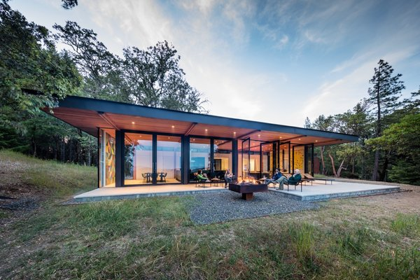 Conceived as an escape from city living, this 2,580-square-foot prefab comprises two primary and 11 secondary modules, while the 290-square-foot guest cabins consist of single modules craned into place atop concrete piers.