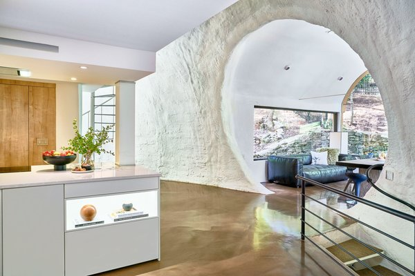 The dome's shape is immediately apparent upon viewing the surrounding walls. In this instance, a circular entrance leads to a living area. The kitchen is painted in Benjamin Moore's Atrium White to match the existing walls.