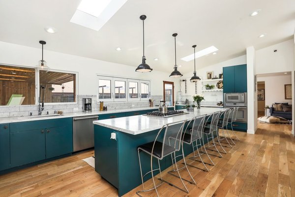 Complete with blue cabinetry, the newly remodeled kitchen features stainless-steel appliances, a marble-topped island, and a line of windows overlooking the covered patio and pool.
