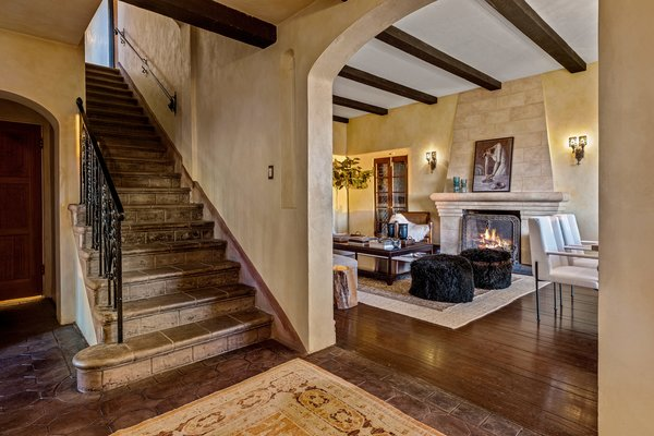 A foyer near the entry leads into the home's main living areas—including a spacious family room, kitchen, and dining room. Original exposed beams line the ceiling throughout.