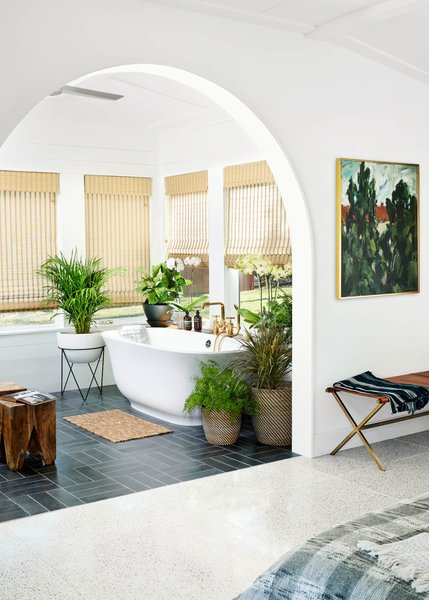 """The sunroom is off the master bath. """"The homeowner asked for a stand-alone tub,"""" Simon says. """"We've done them in the past, but never had a homeowner lead us to install one."""" The bathroom floors are in a parquet pattern from Concrete Collaborative. The wooden benches are from Urban Outfitters, while the leather director's bench is from CB2."""