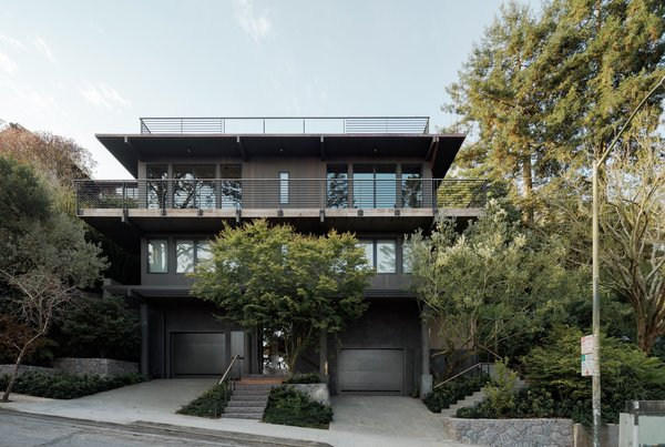 """The home now has new windows, cedar siding, and an upper deck made of wood-capped steel. Theobald also plastered the bottom floor. """"The exposed concrete columns had seams that wrapped around them and looked like paper towels,"""" she says. There was originally no front entryway, so the mason created stairs out of chiseled basalt, matching the backyard stairs and retention walls."""