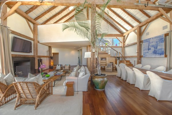 The double-height living/dining room was designed by Tom Flynn. The voluminous space features exposed beams and rafters.