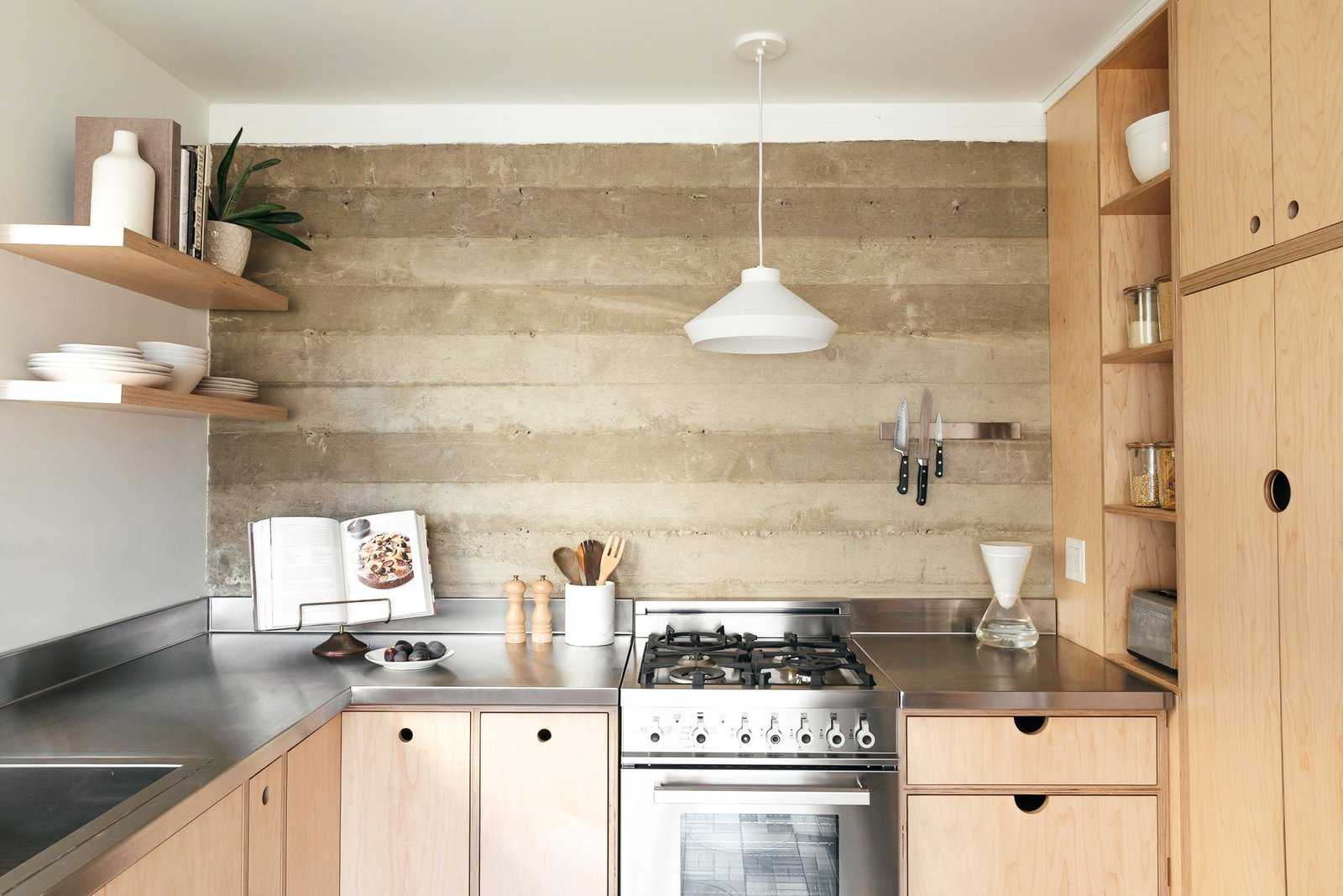 The couple opted for light-hued cabinetry with exposed edges and no hardware, custom-built from marine-grade ApplePly. Having the cabinets custom-made ensured that they could take advantage of every square inch in the small space.