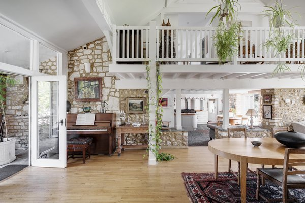 The home welcomes visitors into a double-height entry hall. The bright space makes use of the original barn structure with a spacious, open floor plan and cozy spaces built into alcoves.