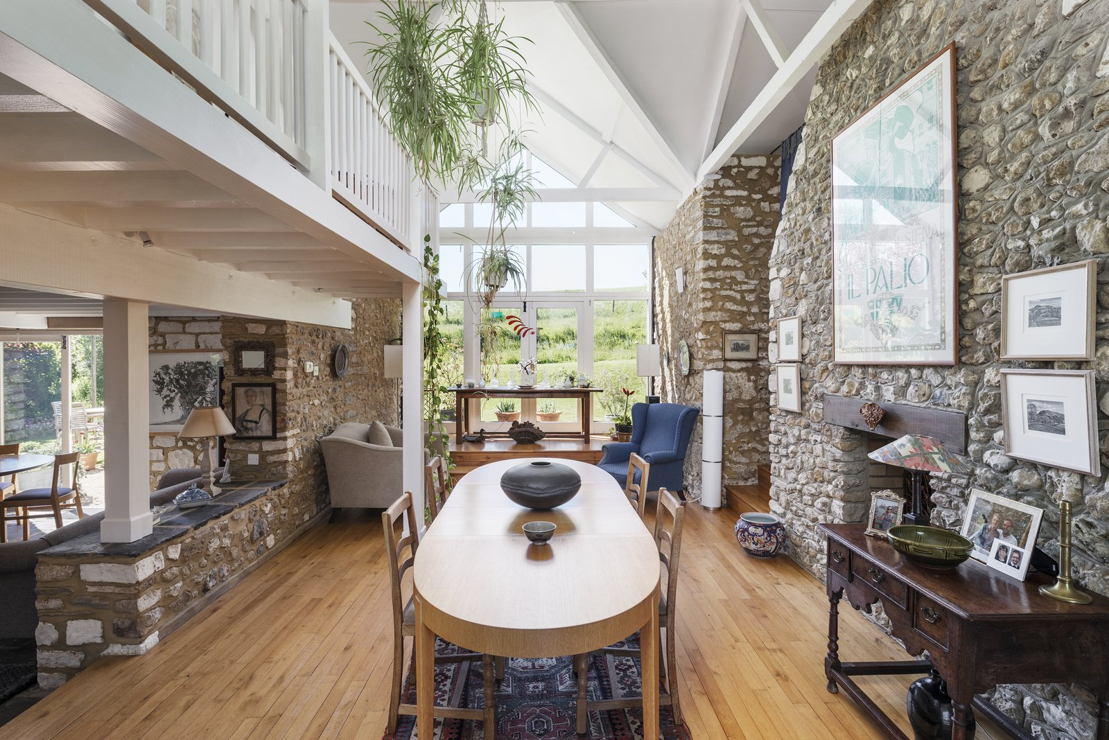 The full-height chimney stack creates a natural division between the dining and living room to the right. A wall of windows caps one end of the space, warming it with natural light and providing picturesque views of the landscape.
