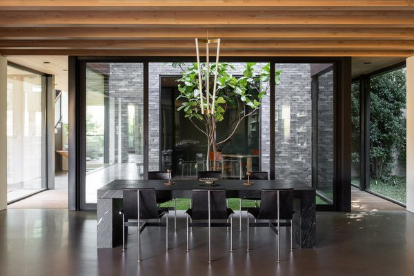 Around the corner from the main entrance, a 23-year-old fiddle leaf fig tree is encased by a glass atrium that pierces the center of the home. The open space directs natural light into both levels of the home—including the dining and living rooms seen here.