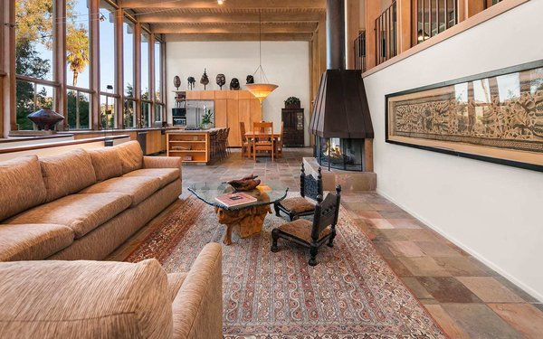 The formal living area features slate tile floors and an original copper-topped fireplace. The large area seamlessly flows into the kitchen and dining room.