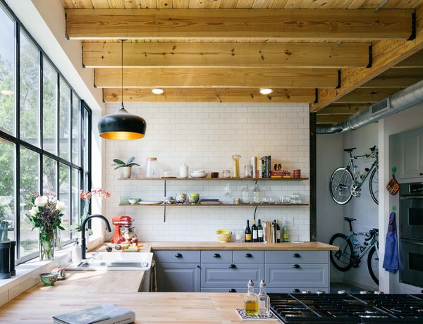 Shane Michael Pavonetti, an Austin-based architect and contractor, and his wife, Holly, built their eco-friendly home on a lean budget of $175,000. The cedar siding used on the exterior reappears throughout the house. Keen on recycling the wood, the couple added shelving to their kitchen as well.