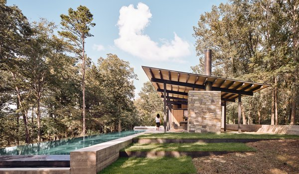 Aegean Pool House's expansive roof structure shelters the indoor/outdoor living spaces beneath it. A freestanding stone fireplace anchors the west side of the living and dining area.