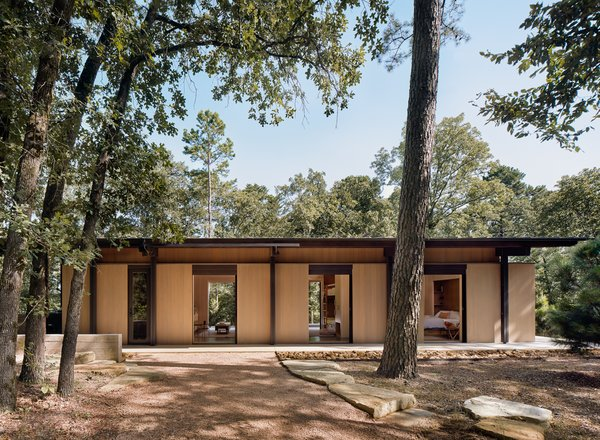 The interior spaces feature large, sliding glass pocket doors on opposite sides of each room that provide generous views of the surrounding forest and lake, and promote cross-ventilation from prevailing breezes from the southeast.