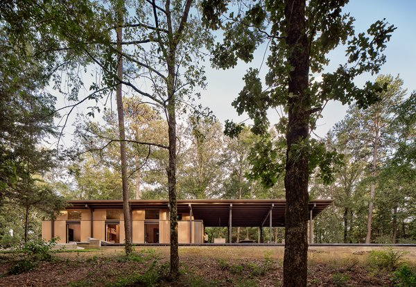The home is carefully sited between tall trees in a pine forest and is split into almost equal areas of indoor and outdoor living space.