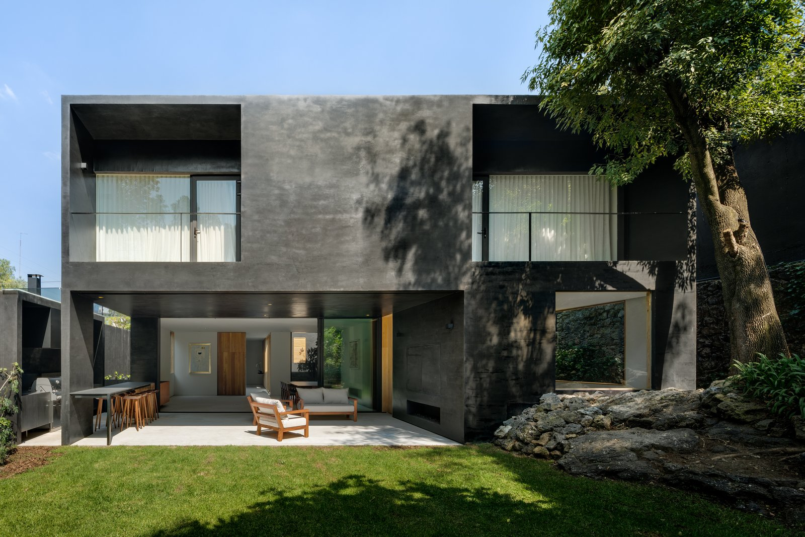 The home embraces its green surroundings with outdoor terraces, open living spaces, and large windows.