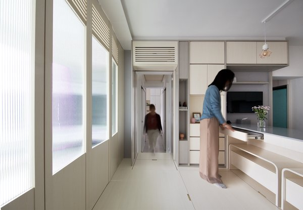 The living room can be completely separated from the open-plan kitchen by closing the timber-and-glass partition. All high-tech features—including the air conditioning unit—are concealed behind timber panels to create a minimal, uncluttered fit-out.