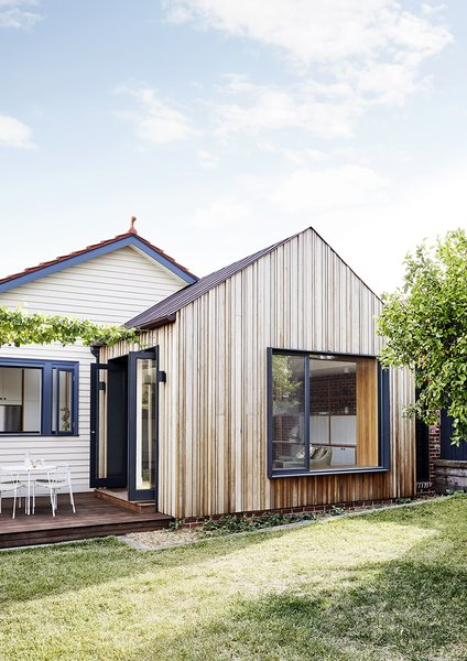 The new addition, only visible from the backyard, echoes the gabled form of the original home. Large openings connect the main living spaces with the backyard.