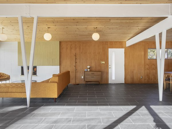 An open floor plan connects the main living spaces, which are subtilely separated by V-shaped support beams. Paneling along the walls complement the wood-clad ceilings.