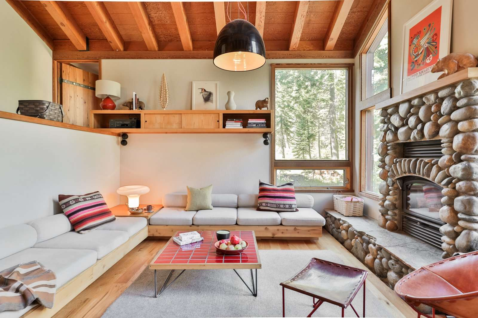 The built-in sofa anchors the living room and faces the existing fireplace. The Leather Oval Chair with a red steel base sits off to the side, and the coffee table was fashioned by attaching vintage steel legs to another tile sample board.