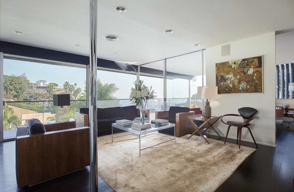The home's top level features a dramatic living room that opens onto a cantilevering balcony. Now available as a monthly rental, the Lew House comes fully furnished with pieces by mid-century design icons such as Kagan, Baughman, Robsjohn-Gibbings, Cherner, and Sciolari.