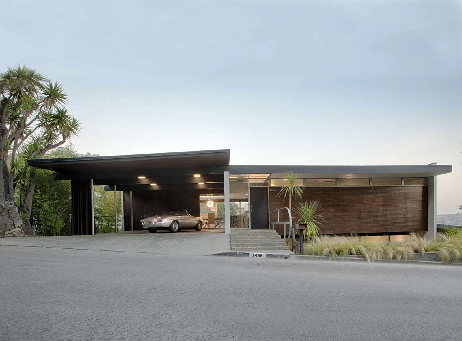 """The 1958 Lew House by Richard Neutra is located at <span style=""""font-family: Theinhardt, -apple-system, BlinkMacSystemFont, &quot;Segoe UI&quot;, Roboto, Oxygen-Sans, Ubuntu, Cantarell, &quot;Helvetica Neue&quot;, sans-serif;"""">1456 Sunset Plaza Drive, just a few turns up from Sunset Boulevard in West Hollywood. The front facade is dominated by a double carport, which Neutra designed with floor-to-ceiling glass along two sides facing the interior.</span>"""
