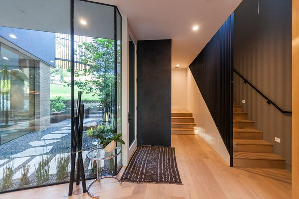 Inside, the home takes on a Zen-like, minimalist aesthetic. A walk from the front yard and underneath the vertical slats reveals a hidden entry courtyard and a heavily glazed interior.