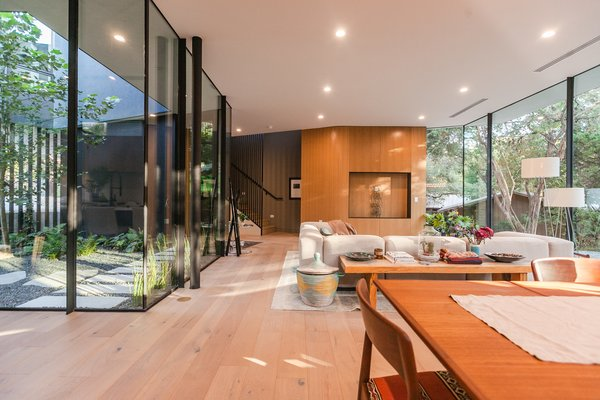 The lower level flows together as a single open space connected by wide-plank white oak flooring and a glazed facade. A large living area is warmed by natural light on both sides.