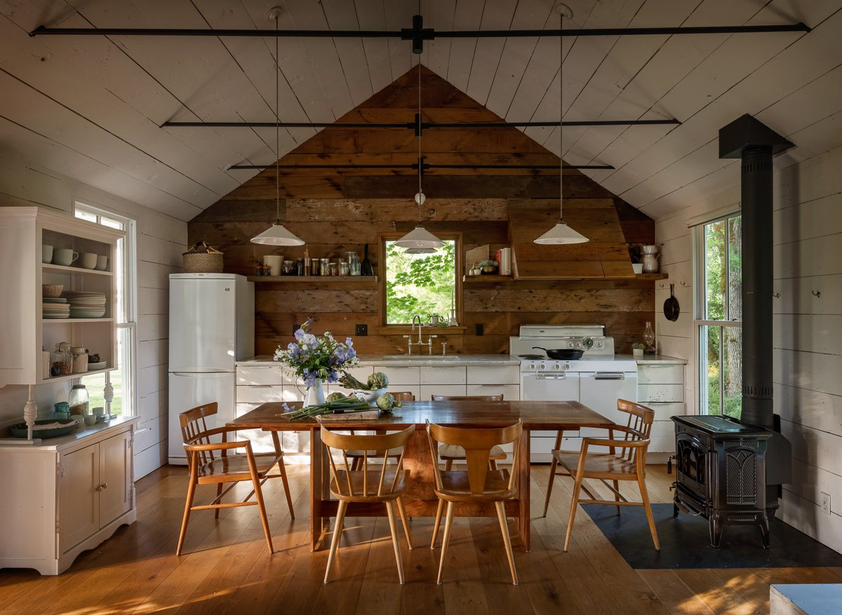 The home's walls are clad in Oregon white oak reclaimed from a dismantled barn on the property. Jessica chose to paint them white to create a bright, airy look, but she left the kitchen wall au naturel for a visual pop. With storage at a premium, the kitchen needed ample cabinetry as well as some ingenious solutions—including a pull-out cabinet hidden in one half of the range hood. A vintage cabinet on the left wall provides open storage for everyday dishes.