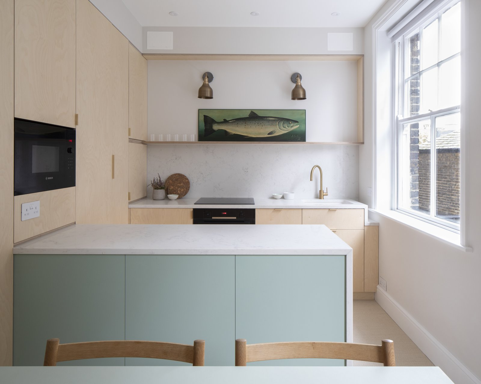 """In the kitchen, bespoke plywood panels wrap IKEA cabinet inserts for a high-end feel on a budget. """"The kitchen is a collection of very intricate details,"""" says Astrain, who fitted the space down to the last available millimeter. The space benefits from two windows now, thanks to the relocated dining area."""