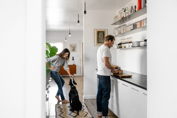 """Darci and Dale in their kitchen with Ricarda, a pup they are fostering during the COVID-19 crisis. """"Our homes are a place of refuge—a manifestation of our lives—and change as we do,"""" says Dale. """"A home allows one to surround themselves with objects that reflect their histories, encounters, and experiences."""""""