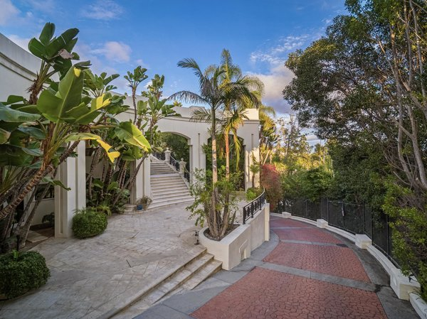 A brick-laid driveway winds up to the main residence. Lush landscaping provides ample privacy.